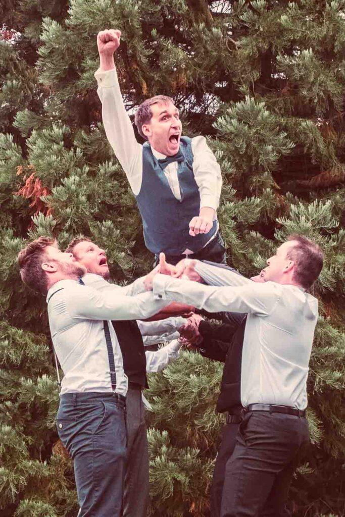 Gäste lassen den Bräutigam auf der Hochzeit hoch leben
